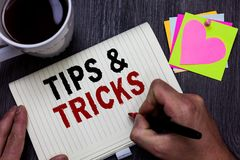 Conceptual hand writing showing Tips and Tricks. Business photo text Steps Lifehacks Handy advice Recommendations Skills Man holdi. Ng marker giving ideas wooden royalty free stock images