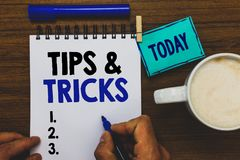 Conceptual hand writing showing Tips and Tricks. Business photo text Steps Lifehacks Handy advice Recommendations Skills Man holdi. Ng marker notebook clothepin stock image