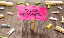 Conceptual hand writing showing To Love Passionately. Business photo showcasing Strong feeling for someone or something else Affec. Tion Paperclip hold pink note royalty free stock photography