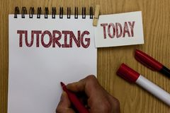 Conceptual hand writing showing Tutoring. Business photo text An act of a person employed to administer knowledge to someone Man h. Olding marker notebook wooden Royalty Free Stock Image