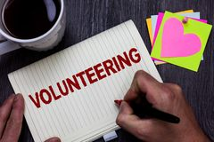 Conceptual hand writing showing Volunteering. Business photo text Provide services for no financial gain Willingly Oblige Man hold royalty free stock image