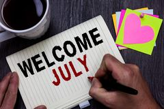 Conceptual hand writing showing Welcome July. Business photo text Calendar Seventh Month 31days Third Quarter New Season Man holdi royalty free stock photos
