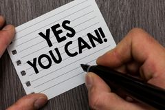 Conceptual hand writing showing Yes You Can. Business photo showcasing Positivity Encouragement Persuade Dare Confidence Uphold Ma. N holding marker notebook royalty free stock image