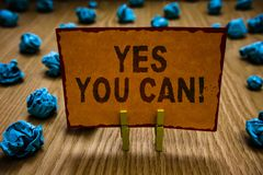 Conceptual hand writing showing Yes You Can. Business photo text Positivity Encouragement Persuade Dare Confidence Uphold Clothesp. Ins holding orange paper note stock photo