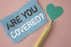 Conceptual hand writing showing Are You Covered Question. Business photo showcasing Health insurance coverage disaster recovery wr. Itten Tear Note paper Pink Stock Image