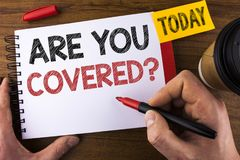 Conceptual hand writing showing Are You Covered Question. Business photo text Health insurance coverage disaster recovery written. By Man Notepad holding Pen Stock Photo