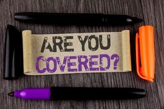 Conceptual hand writing showing Are You Covered Question. Business photo text Health insurance coverage disaster recovery written. Cardboard Paper the wooden Royalty Free Stock Photography
