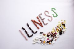 Conceptual Hand writing text caption inspiration Medical care Health concept written with pills drugs capsule word ILLNESS On whit. E  background with space Royalty Free Stock Photography
