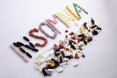 Conceptual Hand writing text caption inspiration Medical care Health concept written with pills drugs capsule word INSOMNIA On whi Royalty Free Stock Photo