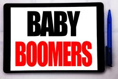 Conceptual hand writing text caption inspiration showing Baby Boomers. Business concept for Demographic Generation written on tabl. Et computer on the white Royalty Free Stock Images