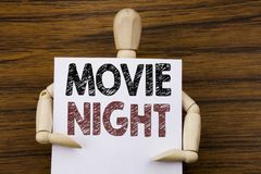 Conceptual hand writing text caption inspiration showing Movie Night. Business concept for Wathing Movies written on sticky note. Paper on wooden background stock image