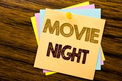 Conceptual hand writing text caption inspiration showing Movie Night. Business concept for Wathing Movies written on sticky note. Paper on wooden background royalty free stock images
