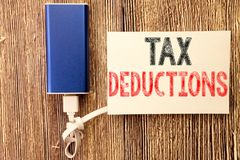 Conceptual hand writing text caption inspiration showing Tax Deductions. Business concept for Finance Incoming Tax Money Deduction. Written on sticky note wood Royalty Free Stock Photo