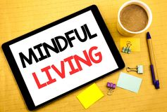 Conceptual hand writing text caption showing Mindful Living. Business concept for Life Happy Awareness Written on tablet laptop, w. Conceptual hand writing text Stock Image