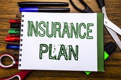 Conceptual hand writing text Insurance Plan.  Concept for Health Life Insured Written on notebook, wooden background with office e. Conceptual hand writing text Stock Photo