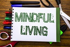 Conceptual hand writing text Mindful Living.  Concept for Life Happy Awareness Written on notebook, wooden background with office. Conceptual hand writing text Royalty Free Stock Photos