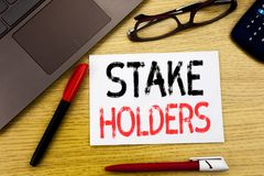Conceptual hand writing text showing Stake Holders. Business concept for Stakeholder Engagement written on paper, wooden backgroun. D in office copy space stock photos
