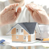 Conceptual Hands Over Miniature House on the Table Royalty Free Stock Photo
