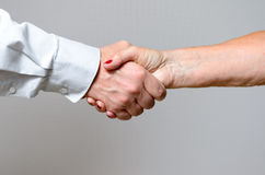 Conceptual Handshake Gesture of Two Adult Hands Stock Photos