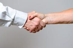Conceptual Handshake Gesture of Two Adult Hands Stock Photos