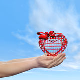 Conceptual human hand with heart and blue sky Stock Photo