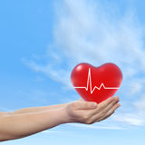 Conceptual human hand with heart and blue sky Stock Image