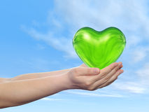 Conceptual human hand with heart and blue sky Stock Photography