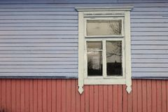 Conceptual image of abandonned home in traditional russian style, colorful wooden wall with monochrome window with rustic white. Concept of abandonned home in stock images