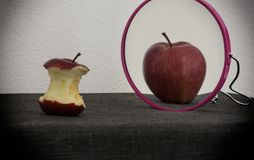Conceptual image of anorexia nervosa using apples. A conceptual image of anorexia nervosa using an apple that see itself really big into mirror royalty free stock images
