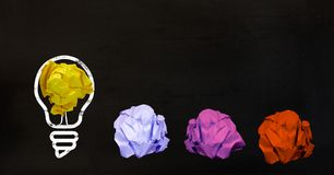 Conceptual image of bulb with multi colored crumpled paper. On black background Royalty Free Stock Images