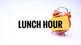 Conceptual image of Business Concept with words Lunch Hour on a clock with a white background. Selective focus. Royalty Free Stock Images