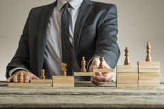Conceptual image of career management. With a businessman forming a bridge of wooden building blocks for chess pieces developing from pawn to king Royalty Free Stock Image
