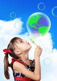 Conceptual image, Child girl blowing soap bubble forming green g Stock Photo