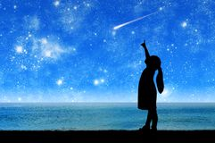Conceptual image of children`s dreams and fantasies. Silhouette, little girl a child standing by the sea looking at the starry sky and pointing a finger at the stock photo