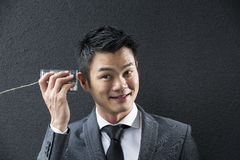 Conceptual image is about communication. Chinese Business man Listening to a Tin Can Phone. Stock Image