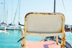 Conceptual Image of Empty Vintage Chair Standing at Sea Harbor Overlooking Marina with Moored Yachts Sailing Boats. Beautiful Sea. Conceptual Image of Empty stock photography