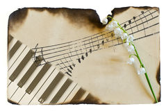 Conceptual image of eternity. The charred paper with a picture of piano keys and notes the flower is Lily of the valley Stock Image