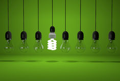 Conceptual image of glowing energy saving bulb and old dark bulb Stock Photo