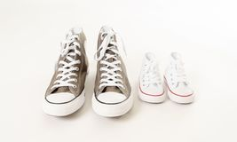 Family sneakers canvas shoes of father and child on white in single parent family concept. Conceptual image of gumshoes sneakers of father and baby son daughter stock photography