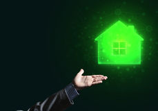 Conceptual image with hand pointing at house or main page icon on dark background. Businessman hand presenting glowing home icon or symbol Royalty Free Stock Photography