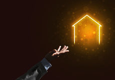 Conceptual image with hand pointing at house or main page icon on dark background. Businessman hand presenting glowing home icon or symbol Stock Photo