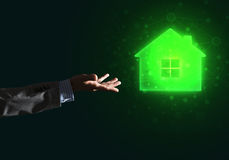 Conceptual image with hand pointing at house or main page icon on dark background. Hand of businessman touching with finger glowing home icon or symbol Stock Image