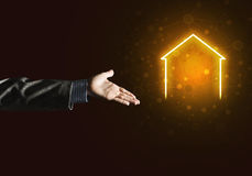 Conceptual image with hand pointing at house or main page icon on dark background Stock Images
