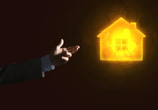Conceptual image with hand pointing at house or main page icon on dark background Royalty Free Stock Photography