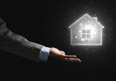 Conceptual image with hand pointing at house or main page icon on dark background Stock Photography