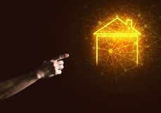 Conceptual image with hand pointing at house or main page icon on dark background. Hand of man touching with finger glowing home icon or symbol Royalty Free Stock Image