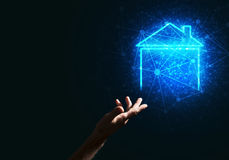 Conceptual image with hand pointing at house or main page icon on dark background Royalty Free Stock Image