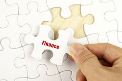 Conceptual image with hand and puzzle. Finance concept. Hand holding piece of jigsaw puzzle showing FINANCE word Royalty Free Stock Photo