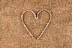 Conceptual image of the heart made in rope lying on sackcloth Royalty Free Stock Photography