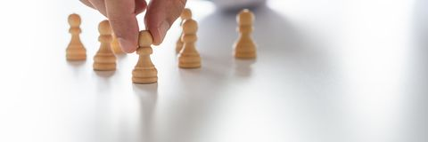 Conceptual image of human resources and recruiting. Wide view image of male hand positioning pawn chess pieces in a conceptual image of human resources and royalty free stock images